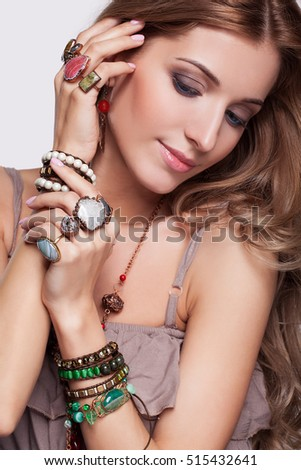 Portrait of beautiful young brunette woman dressed in boho style  in  jewelry and  bijouterie on gray background