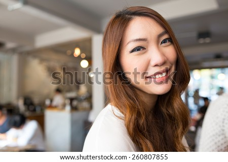 Portrait of beautiful young brunette woman in cafe restaurant. - stock photo