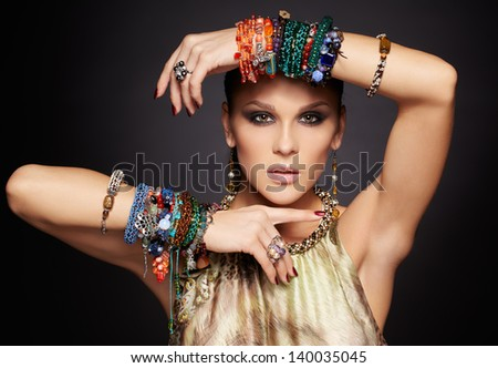 portrait of beautiful young brunette woman in multiple bracelets and ear-rings on dark gray - stock photo