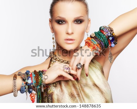 portrait of beautiful young brunette woman in multiple bracelets and other jewelry on gray - stock photo