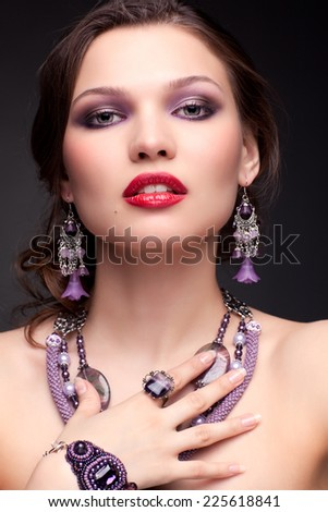 Portrait of beautiful young brunette woman in necklace and earrings on dark gray background