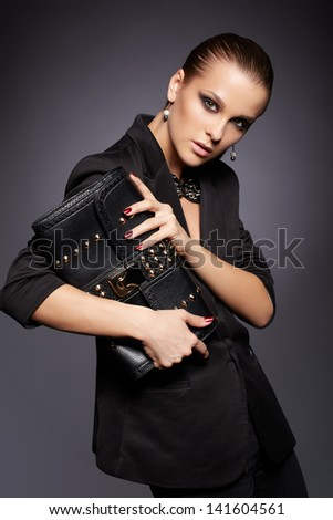 portrait of beautiful young brunette woman in stylish black jacket with leather clutch on dark gray - stock photo