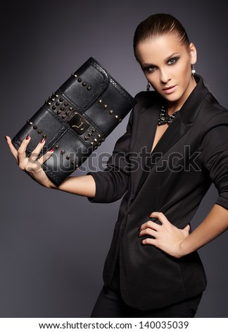 portrait of beautiful young brunette woman in stylish black jacket with leather clutch on gray - stock photo