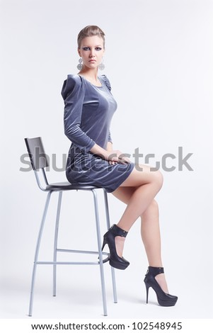 portrait of beautiful young brunette woman in stylish dress and court shoes sitting on bar chair - stock photo