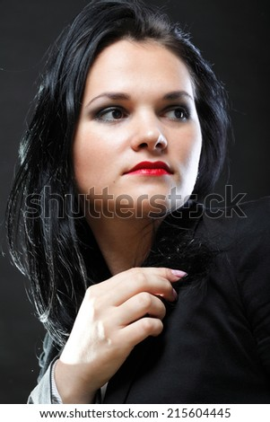 portrait of beautiful young brunette woman on black background. - stock photo