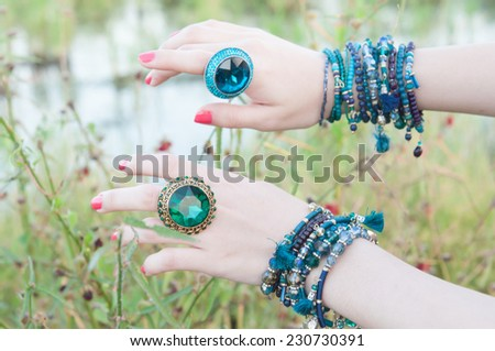portrait of beautiful young brunette woman posing in rings and multiple bracelets - stock photo