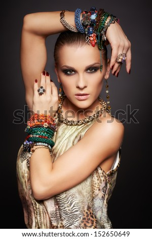 portrait of beautiful young brunette woman posing in rings, collar, ear-rings and multiple bracelets - stock photo