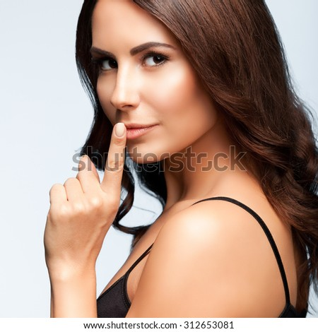 portrait of beautiful young brunette woman with finger on lips, on bright grey background, square composition - stock photo
