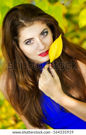 Portrait of beautiful young brunette woman with long hair wearing a blue knitted dress on a background of autumn nature