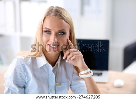 Portrait of beautiful young business woman working on a laptop. - stock photo
