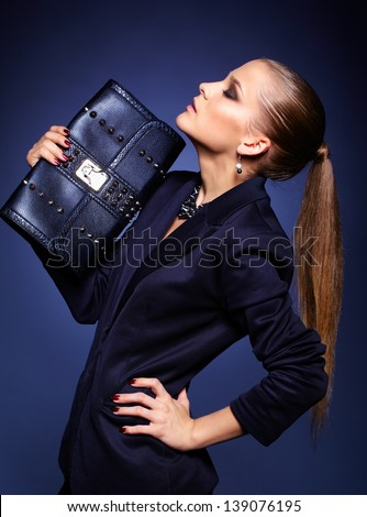 Portrait of beautiful young businesswoman on blue with purse - stock photo