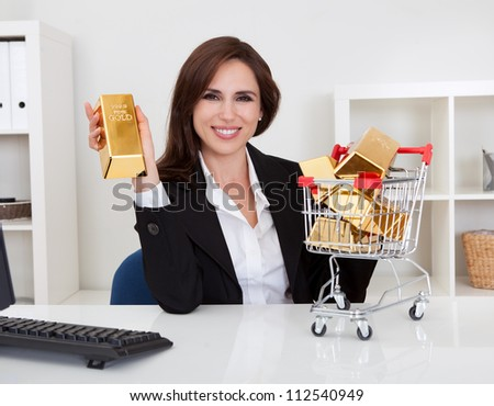 Portrait of beautiful young businesswoman presenting gold bars in mini shopping cart - stock photo