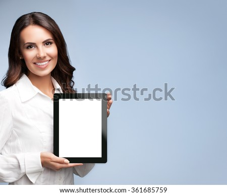 Portrait of beautiful young businesswoman showing blank no-name tablet pc monitor, over grey background, with copyspace area for slogan or text message