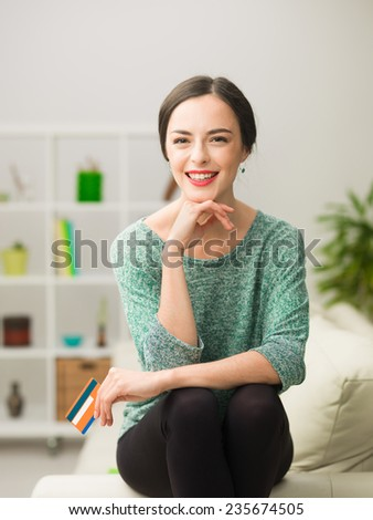 portrait of beautiful young caucasian woman sitting on sofa at home, smiling and holding credit card - stock photo