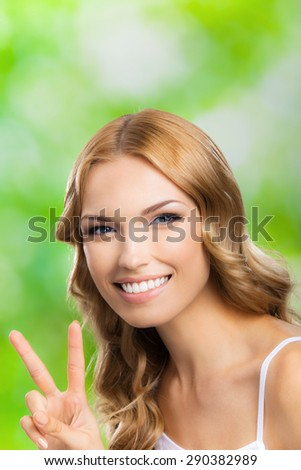 Portrait of beautiful young cheerful blond woman, showing two fingers or victory gesture, outdoors - stock photo