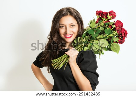 Portrait of beautiful young cheerful woman with a bouquet of roses - stock photo