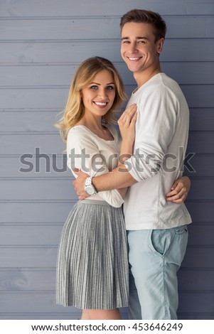 Portrait of beautiful young couple in casual clothes hugging, looking at camera and smiling, standing against gray wall - stock photo