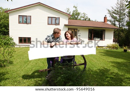 Portrait of beautiful young couple in front of house