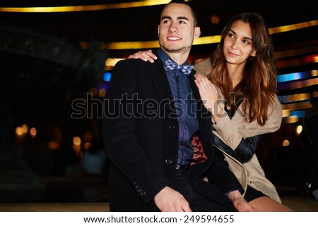 Portrait of beautiful young couple looking away in the night city with beautiful lights on background, romantic couple at night walk on Valentine's Day - stock photo