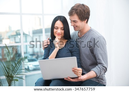 Portrait of beautiful young couple. Man and woman sitting near big window with laptop at home. Couple feeling comfortable and smiling - stock photo
