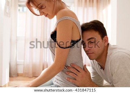 Portrait of beautiful young couple relaxing together in home bedroom, being affectionate and loving indoors. Boyfriend girlfriend in love, enjoying intimate sensuality in bed, home lifestyle interior. - stock photo