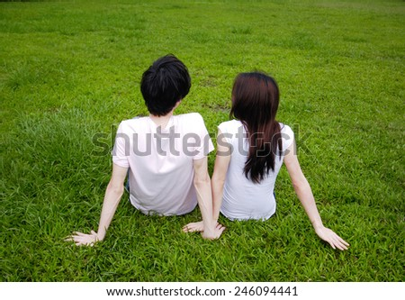 Portrait of beautiful young couple sitting in park relaxing - stock photo