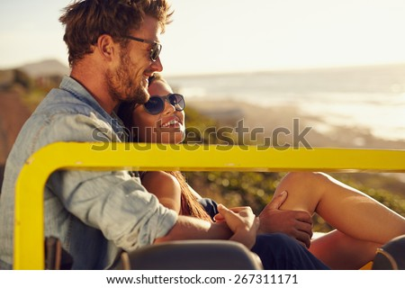 Portrait of beautiful young couple sitting together in a car smiling on a summer day. Romantic young couple enjoying the each others company outdoors. - stock photo