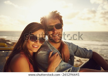 Portrait of beautiful young couple wearing sunglasses looking at camera while on a road trip. Young man and woman with beach in background. - stock photo