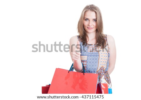 Portrait of beautiful young customer showing thumb up and holding colored shopping bags with copyspace isolated on white - stock photo