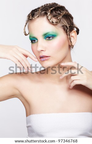 portrait of beautiful young dark blonde woman with creative braid hairdo and green eye shades touching her cheek