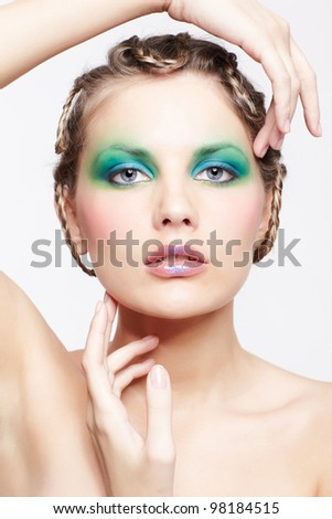 portrait of beautiful young dark blonde woman with creative braid hairdo and green eye shades touching her jaw and temple