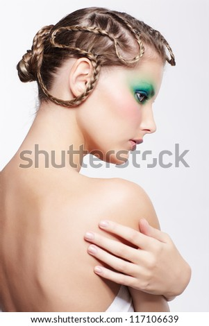 portrait of beautiful young dark blonde woman with creative braid hairdo and green eye shades make up