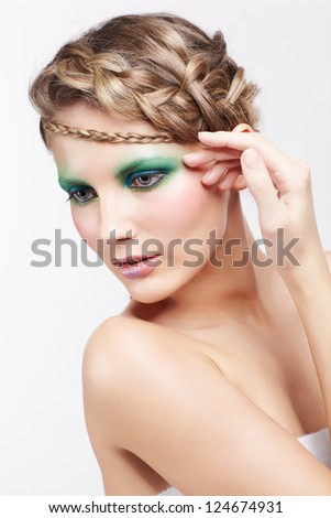 portrait of beautiful young dark blonde woman with creative braid hairdo and green eye shades make-up  posing on gray