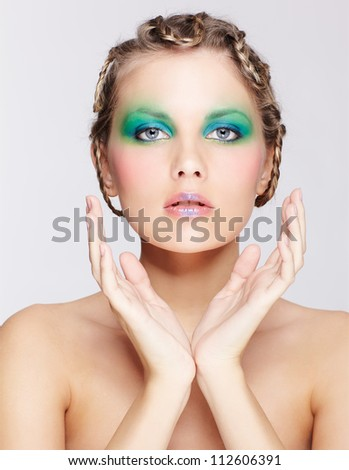 portrait of beautiful young dark blonde woman with creative braid hairdo and green make-up posing on gray