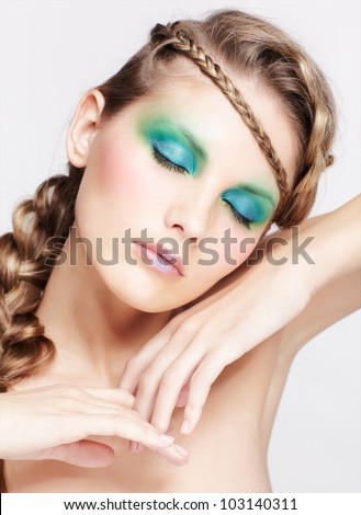 portrait of beautiful young dark blonde woman with creative braid hairdo posing on gray with eyes closed