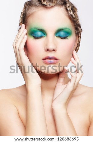 portrait of beautiful young dark blonde woman with creative braid hairdo touching her face and closing eyes