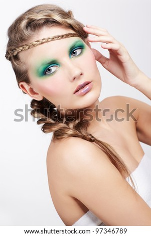 portrait of beautiful young dark blonde woman with creative plait hairdo and green eye shades make-up