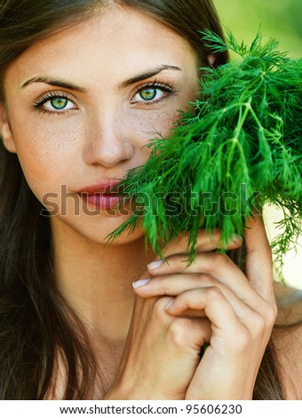 portrait of beautiful young dark-haired sexy girl seductively baring her shoulders with bundle of herbs (dill) in hands - stock photo