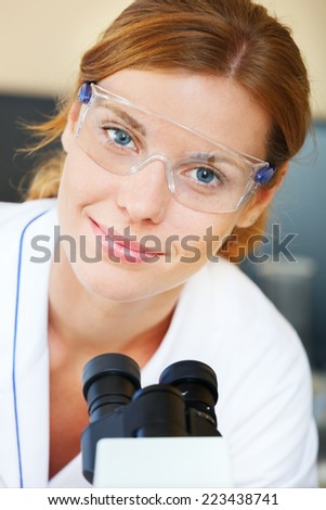 Portrait of beautiful young doctor in a laboratory with microscope looking at camera - stock photo