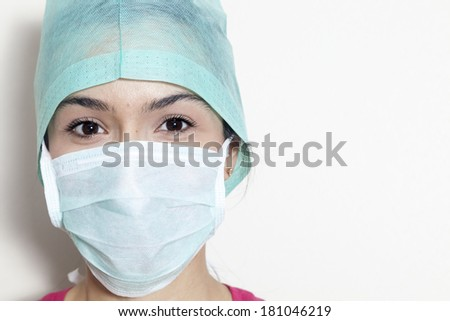 Portrait of beautiful young doctor smiling wearing mask and bonnet - stock photo