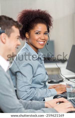 Portrait of beautiful young employee with male colleague working in call center - stock photo