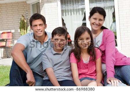 Portrait of beautiful young family of four sitting together outside their home
