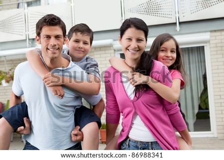 Portrait of beautiful young family together outside their house - stock photo