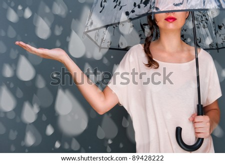 Portrait of beautiful young fashionable woman standing under umbrella and catching fake water drops of rain. Safety concept - stock photo