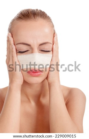 portrait of beautiful young female face with bandage on her nose - stock photo