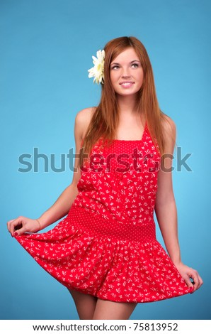 Portrait of beautiful young female in red sundress over blue background - stock photo