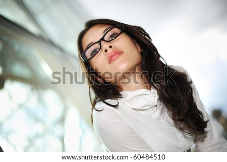 Portrait of beautiful young female model posing outside on blurred background. Shallow DOF, focus on lips. - stock photo