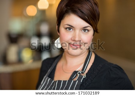 Portrait of beautiful young female owner smiling in cafe - stock photo