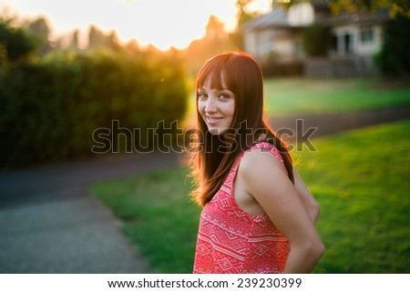 portrait of beautiful young female  smiling at camera sun behind head - stock photo
