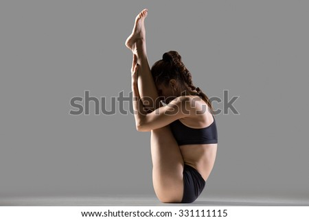 Portrait of beautiful young fit woman in sportswear doing sport exercise, sitting in upward facing forward bend posture (urdhva mukha paschimottanasana), studio, gray background - stock photo